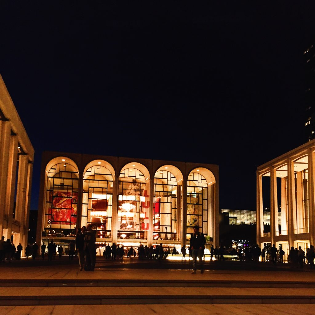 photo of Lincoln Center plaza at night with crowds walking in front of Met Opera House
