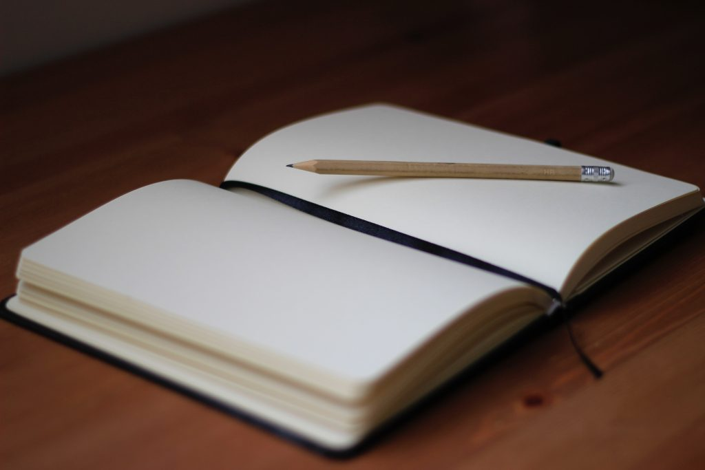 open notebook with blank pages and pencil resting on top of it
