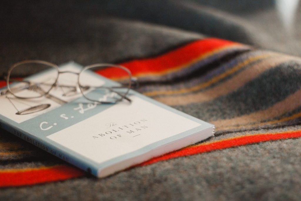 C. S. Lewis's book on top of a blanket with glasses resting on top of it