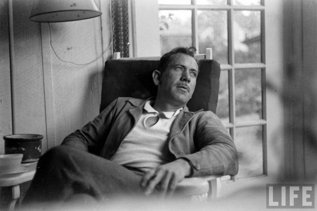 Photo of John Steinbeck reclining in a chair in front of a window