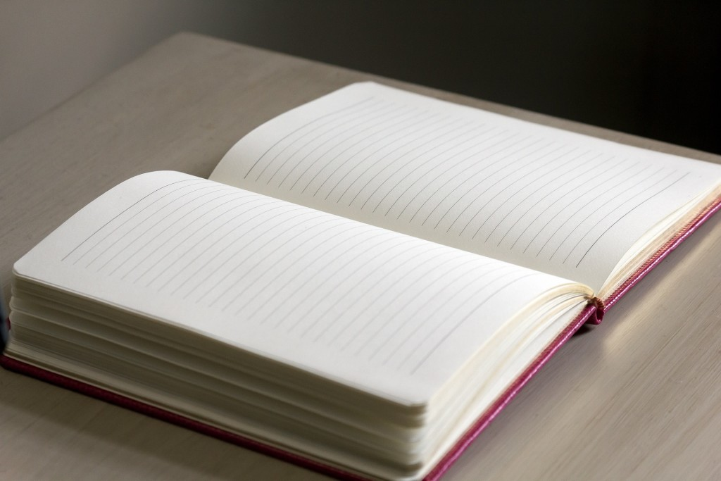 Open notebook with blank pages on top of table