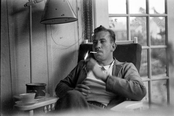 Photo of John Steinbeck lighting a cigarette