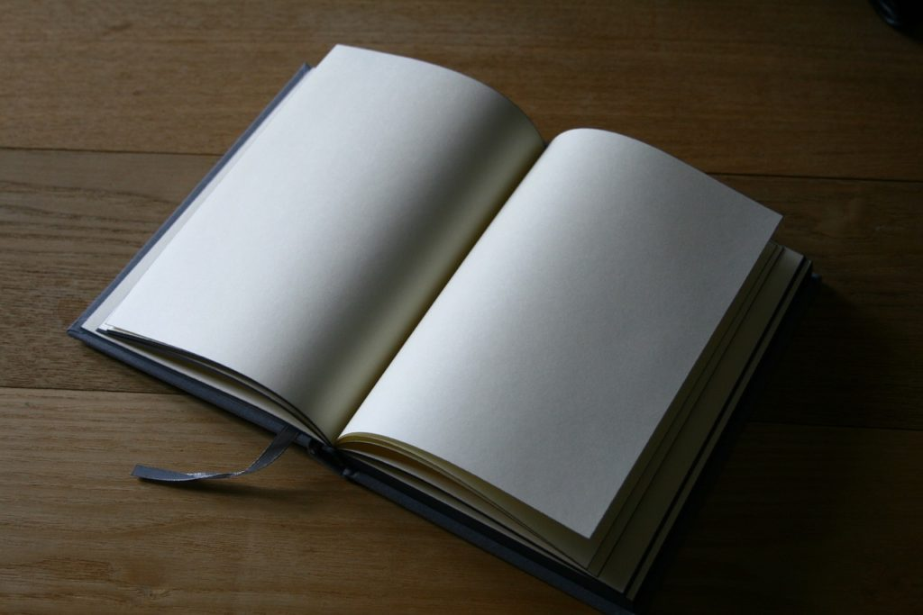 Open journal on table with blank white pages