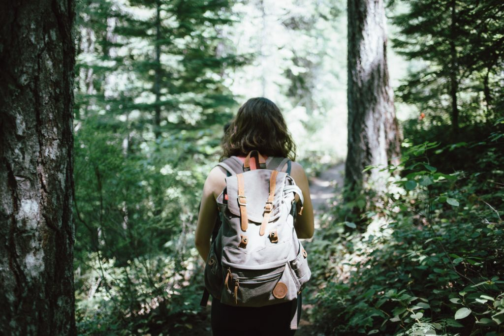 Woman wearing backpack walking in a forest