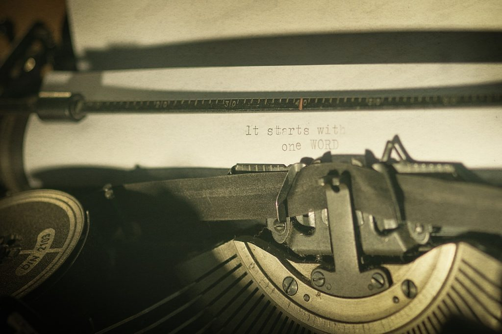 """Closeup of paper in a typewriter displaying sentence """"It starts with one word"""""""