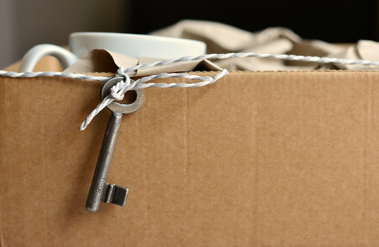 Box of packaged items with key dangling from piece of twine