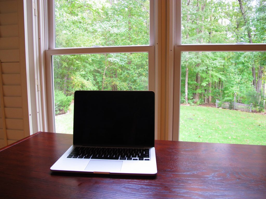 Laptop on top of empty desk in front of window looking out on forest