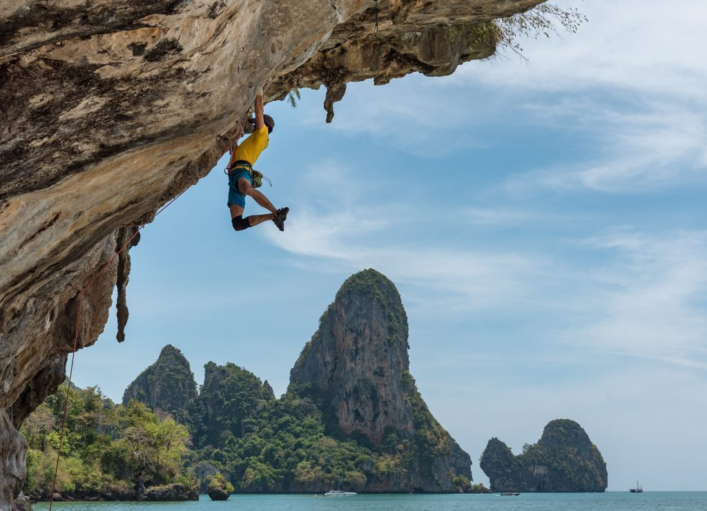Man rock climbing and hanging off mountain