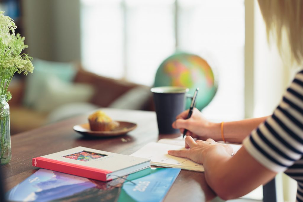 Woman writing in notebook at desk next to globe, muffins on plate, books