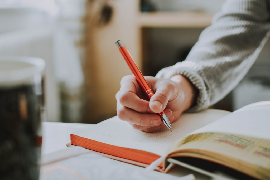 Person holding red pen and writing in journal | How to Find New Blog Post Ideas When You're Stuck