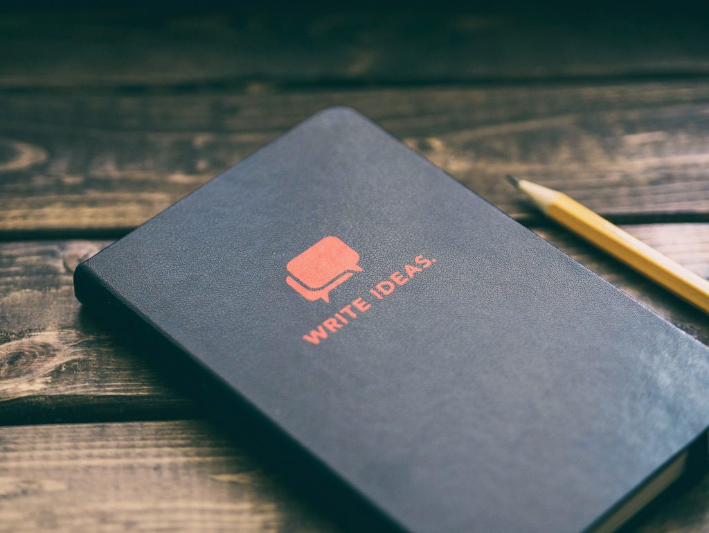 Black journal and yellow pencil on wooden table. | 8 Strategies That Will Help You Improve Your Writing Skills