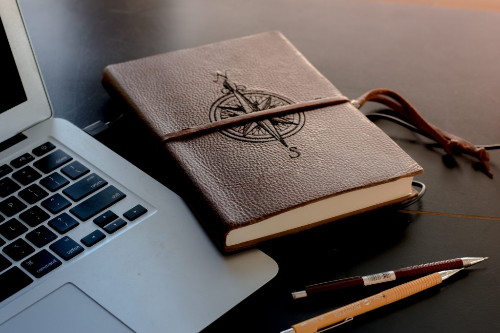 Brown leather journal with compass on cover rests on top of a laptop | Two Essential Journals That Will Help You Achieve Your Goals