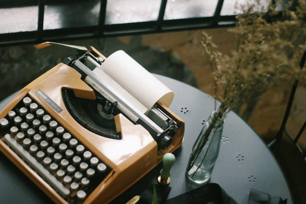 Yellow typewrite on table next to vase