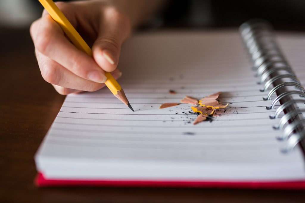 Hand gripping sharpened pencil and writing in notebook | 5 Exercises From Famous Authors That Will Improve Your Writing