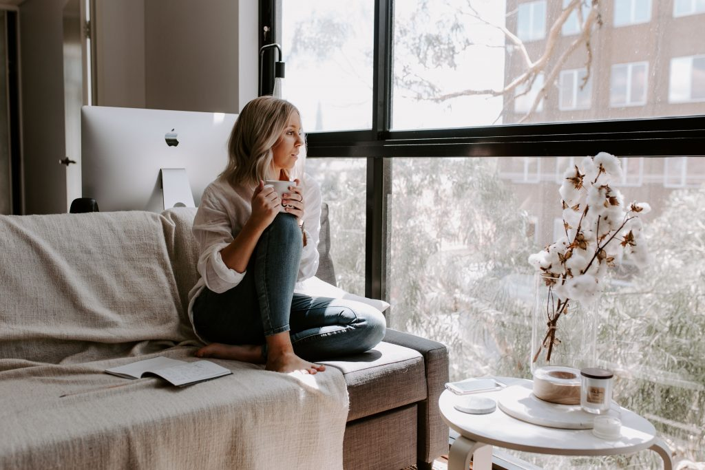 Woman sitting on couch holding mug and looking out window