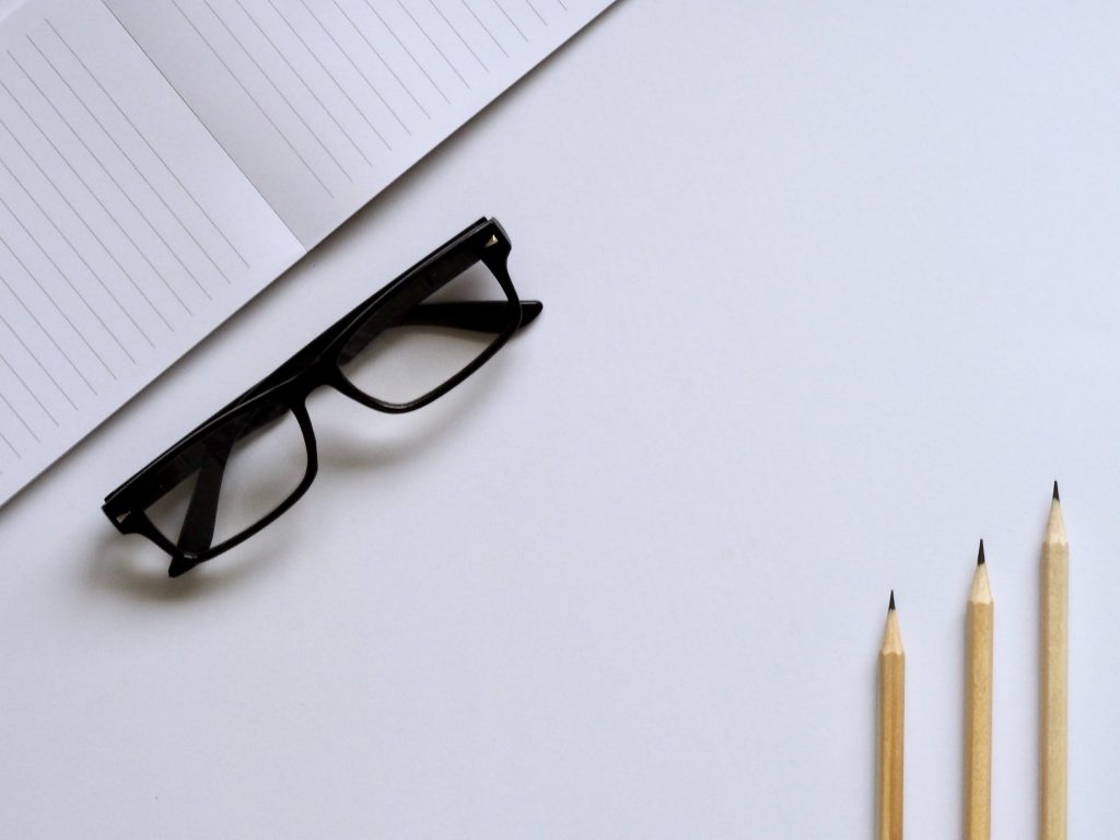 Blank notebook next to pair of glasses and three sharpened pencils | 7 Editing Tips That Will Make Your Writing More Engaging